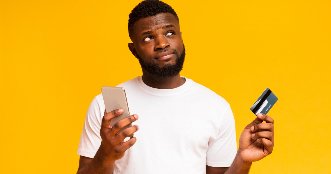 Young man with credit card and phone